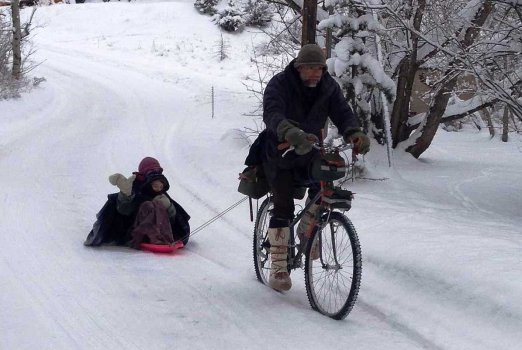 Deacon Patrick wearing Steger Mukluks while biking and pulling kids in a sled